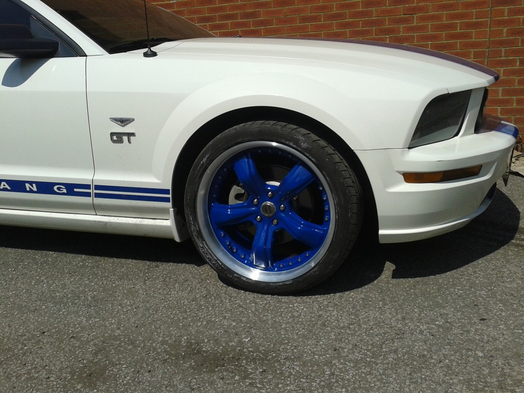 picture of the front of a Ford Mustang with blue split rims