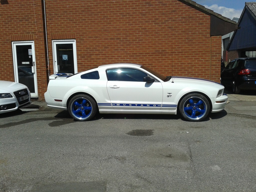 picture of a Ford Mustang with blue split rims
